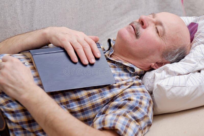 睡觉在有书的沙发的老人 库存图片