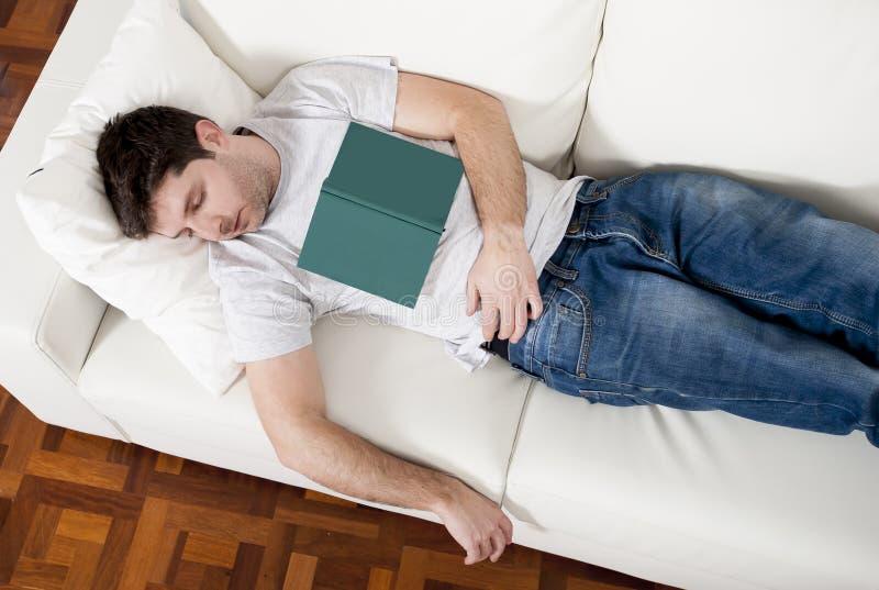 睡觉在有书的长沙发的疲乏的年轻人在膝部 免版税库存图片
