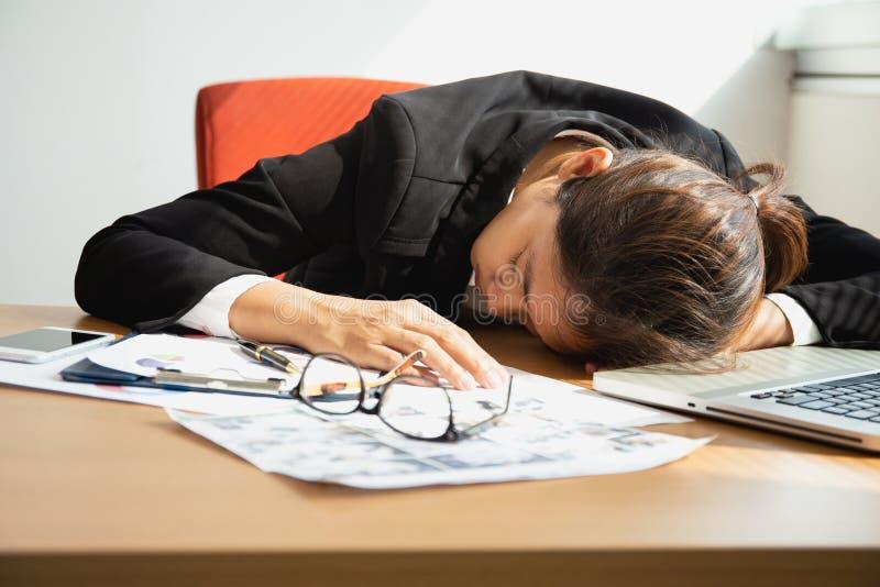 睡觉在有膝上型计算机的工作书桌的女实业家吃完午饭计时 库存照片