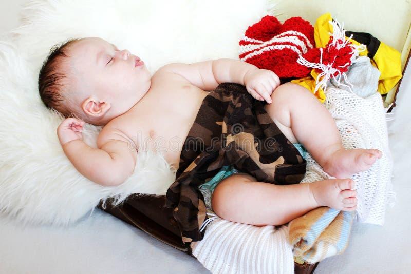 睡觉在有衣裳的手提箱的3个月的可爱的婴孩年龄 免版税图库摄影
