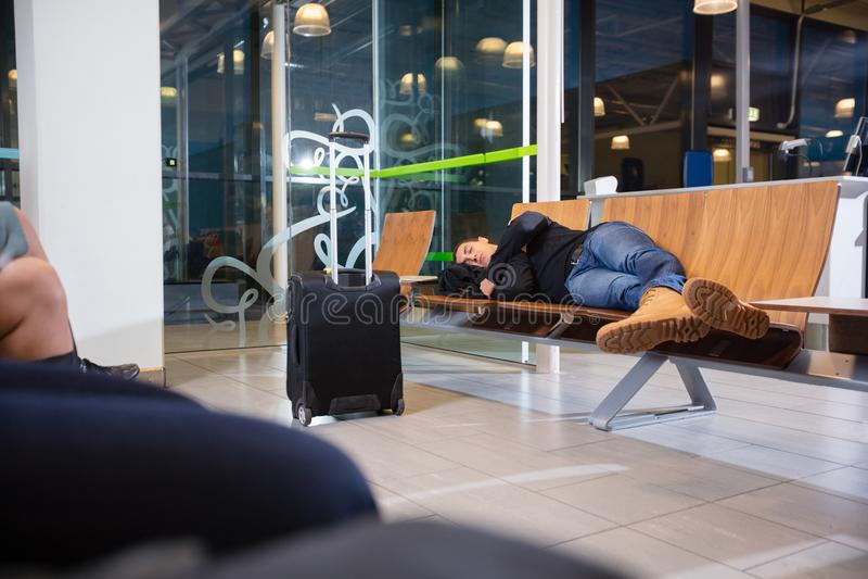 睡觉在机场等候室的年轻人 库存照片