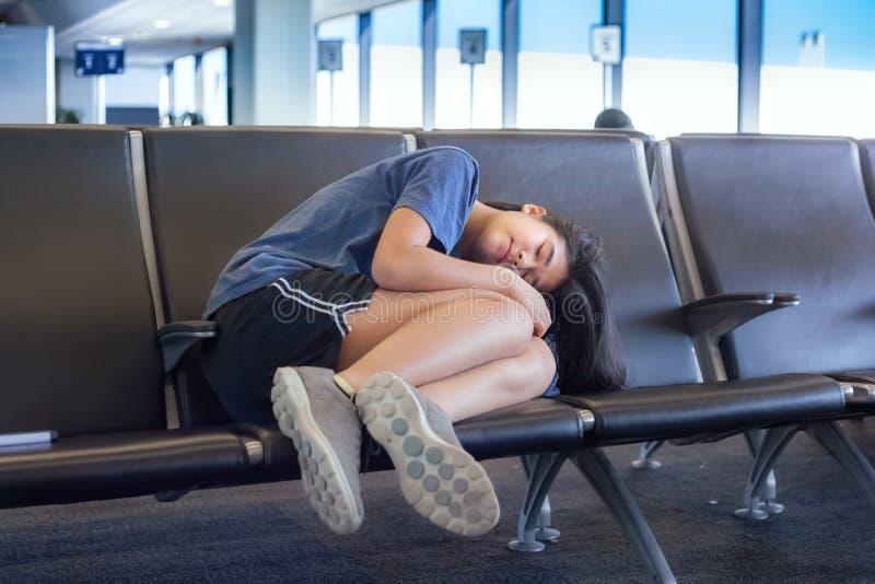睡觉在机场长凳的十几岁的女孩在终端,疲倦 免版税库存图片