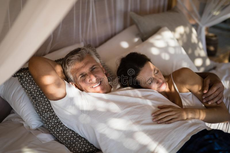 睡觉在机盖床上的资深夫妇 免版税库存照片