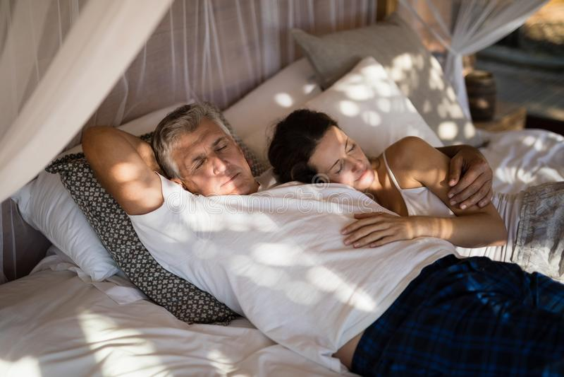 睡觉在机盖床上的资深夫妇 免版税图库摄影