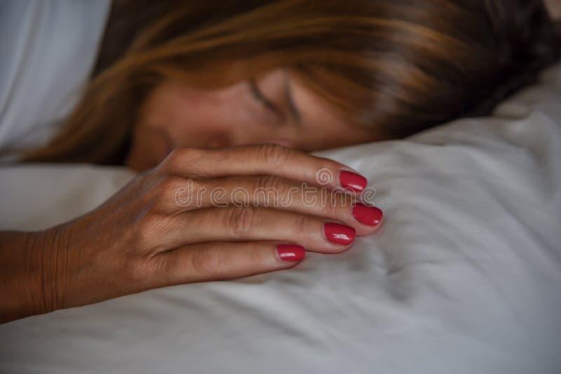睡觉在枕头的妇女 库存照片