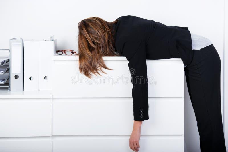 睡觉在柜台的女实业家 免版税库存图片