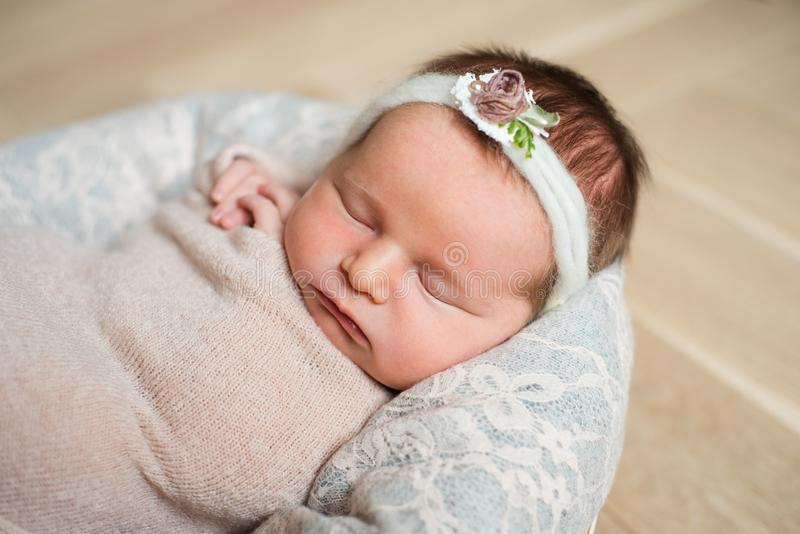 睡觉在桃红色背景的新出生的逗人喜爱的女孩 库存照片