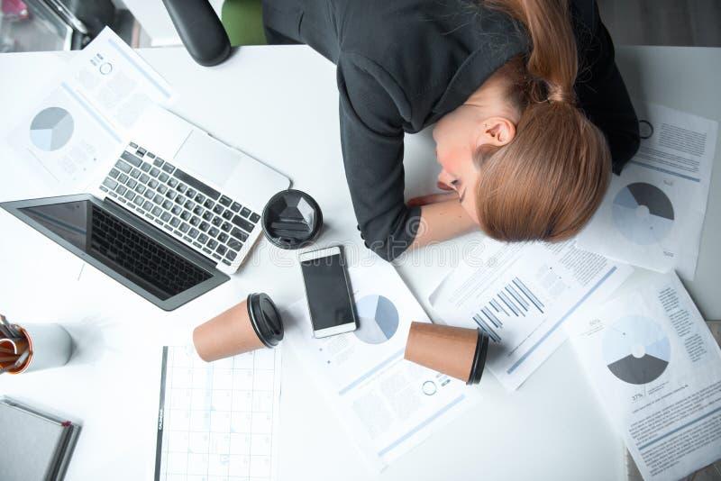睡觉在桌上的严肃的疲乏的女实业家 免版税库存图片