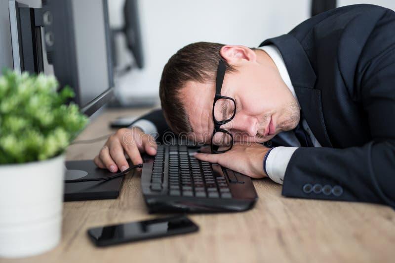 睡觉在桌上的疲乏的商人接近的画象在现代办公室 免版税图库摄影