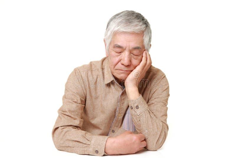 睡觉在桌上的资深日本人 图库摄影