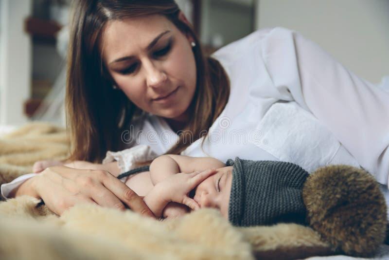睡觉在毯子的婴孩,当她的母亲看时 免版税库存图片