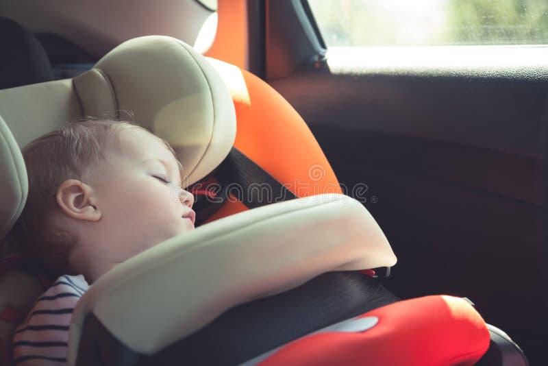 睡觉在汽车安全位子的婴孩,当旅行时 免版税图库摄影