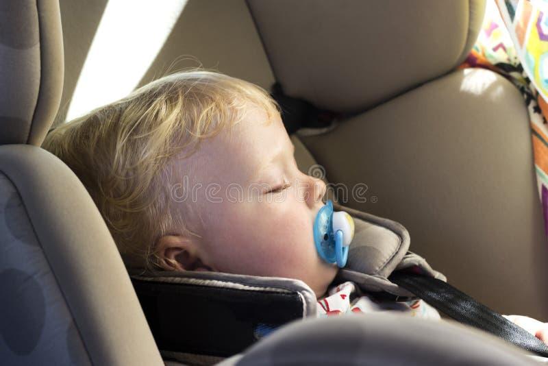 睡觉在汽车座位的白肤金发的婴孩 免版税库存照片