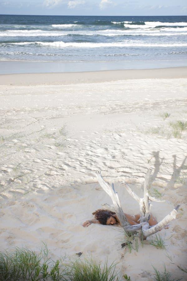 睡觉在海滩的沙子的裸体小姐 库存照片