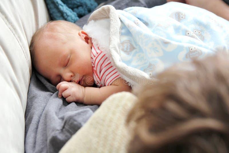 睡觉在父亲的胳膊的新出生的女婴 免版税库存图片