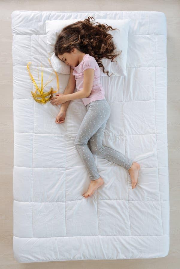 睡觉在狂欢节面具附近的好逗人喜爱的女孩 库存照片