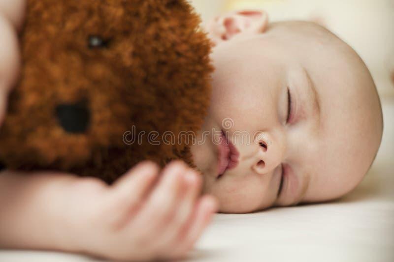 睡觉在甜睡眠的逗人喜爱的矮小的婴孩拥抱熊 免版税图库摄影