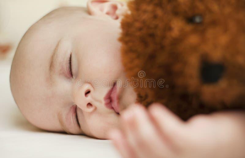 睡觉在甜睡眠的逗人喜爱的矮小的婴孩拥抱熊 库存照片