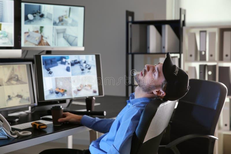 睡觉在监视屋子里的保安 库存图片