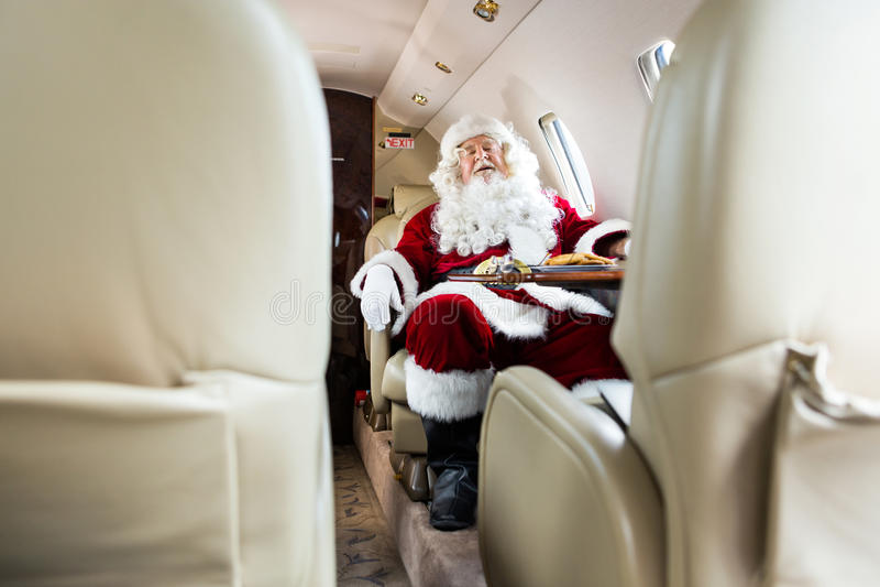 睡觉在私人喷气式飞机的圣诞老人 免版税图库摄影