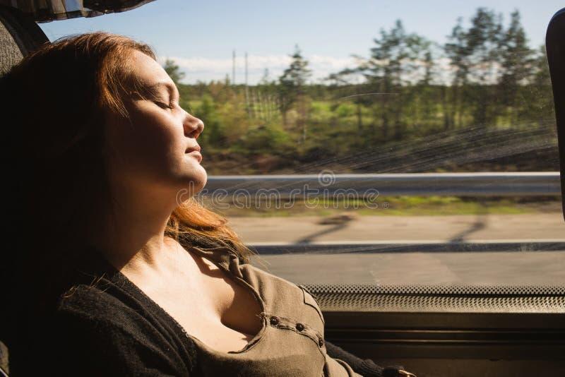 睡觉在窗口旁边的一次公共汽车旅行的旅客妇女 长的移动的概念 库存照片