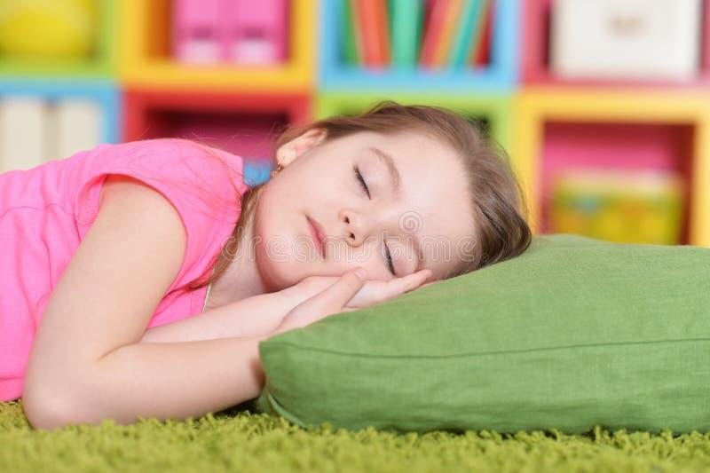 睡觉在绿色地毯的逗人喜爱的女孩 免版税库存图片