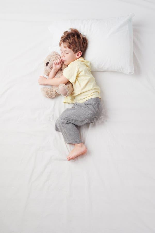 睡觉在胎儿姿势的小男孩顶视图 库存图片