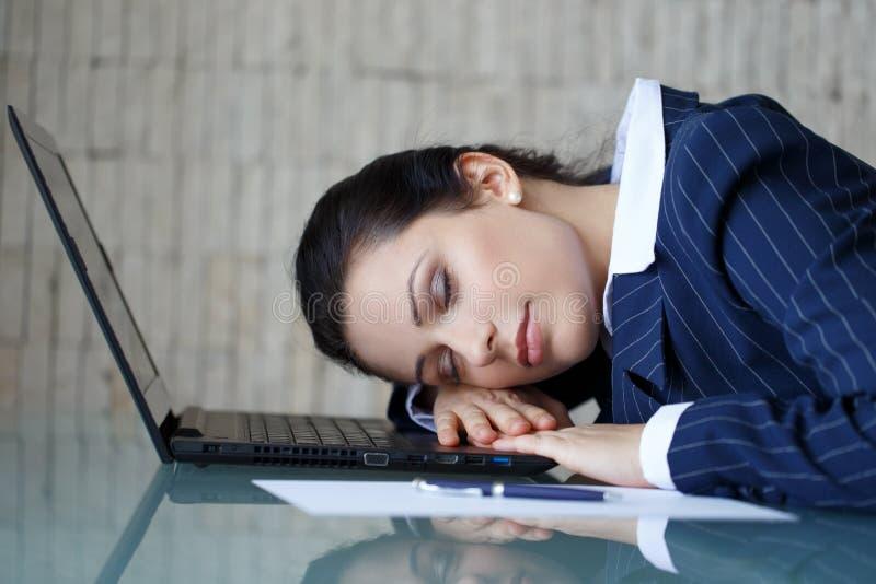 睡觉在膝上型计算机的女实业家 库存照片