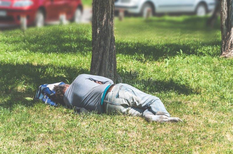 睡觉在草的老赤足无家可归者或难民人在城市公园使用他的旅行袋子作为枕头,社会新闻纪录片的str 免版税图库摄影