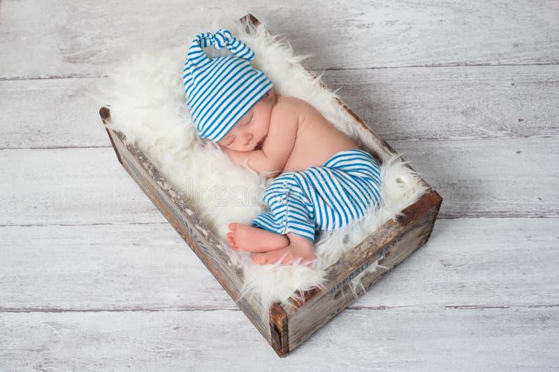 睡觉新出生的婴孩佩带的睡衣 免版税库存图片