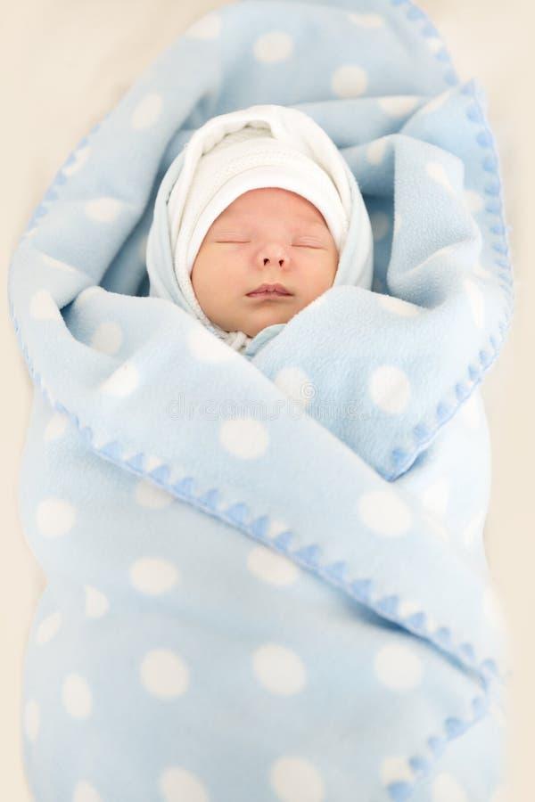 睡觉在蓝色被删去的,新出生的孩子画象的新生儿 库存照片