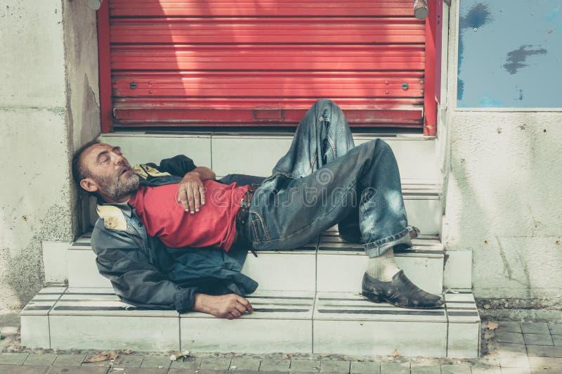 睡觉在街道上的台阶的可怜的无家可归的人或难民,社会新闻纪录片的概念 免版税库存图片