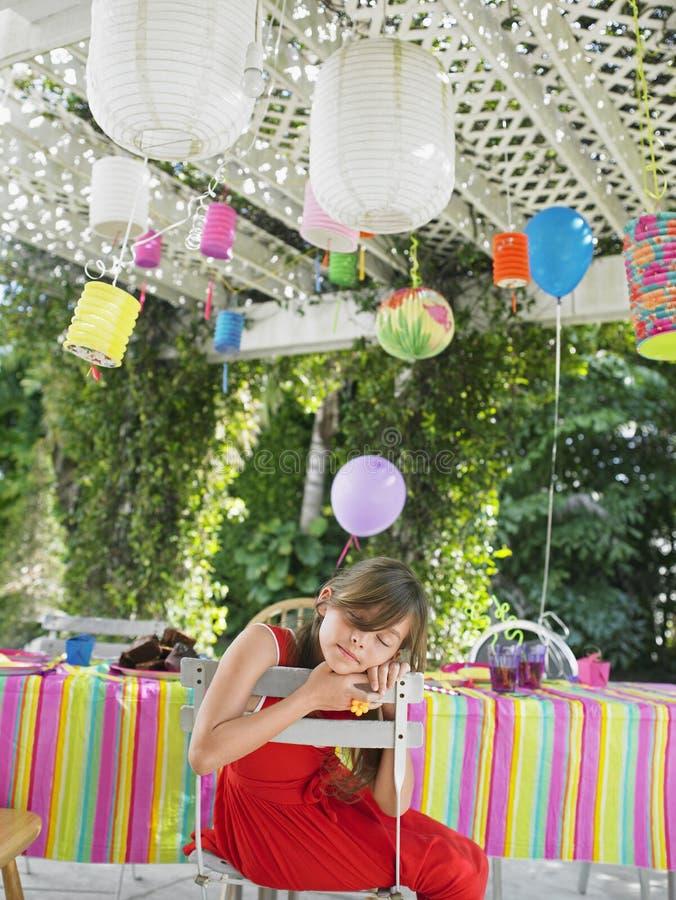 睡觉在表上的女孩在生日聚会以后 库存图片