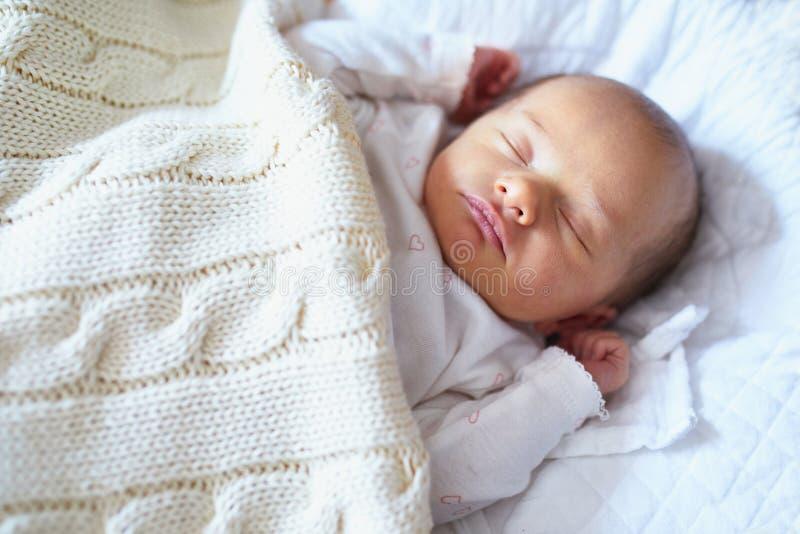 睡觉在被编织的毯子下的新出生的婴孩 图库摄影