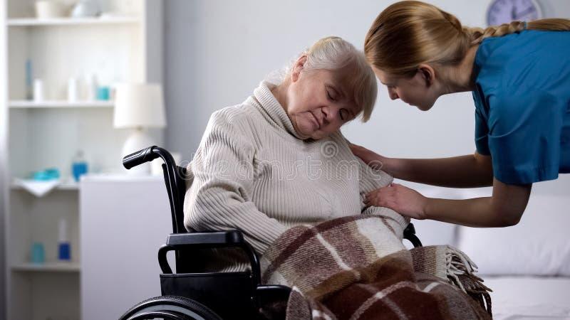 睡觉在轮椅,医院护理的年轻志愿醒的老妇人 免版税库存图片
