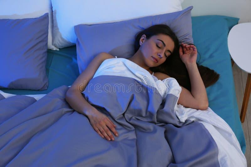 睡觉在软的枕头的年轻女人在晚上 免版税库存照片