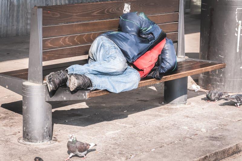 睡觉在都市街道上的长木凳的可怜的无家可归的人或难民在城市,社会新闻纪录片的概念 库存照片