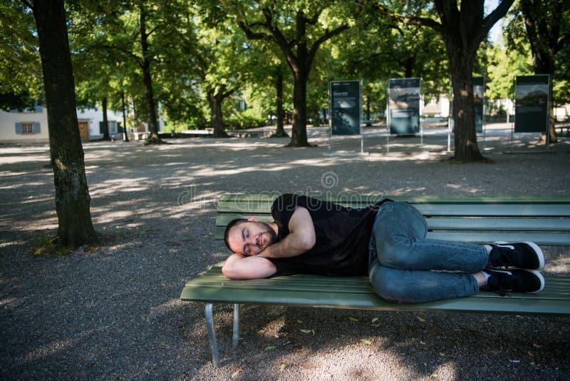 睡觉在长木凳的可怜的无家可归的人在公园 免版税库存图片
