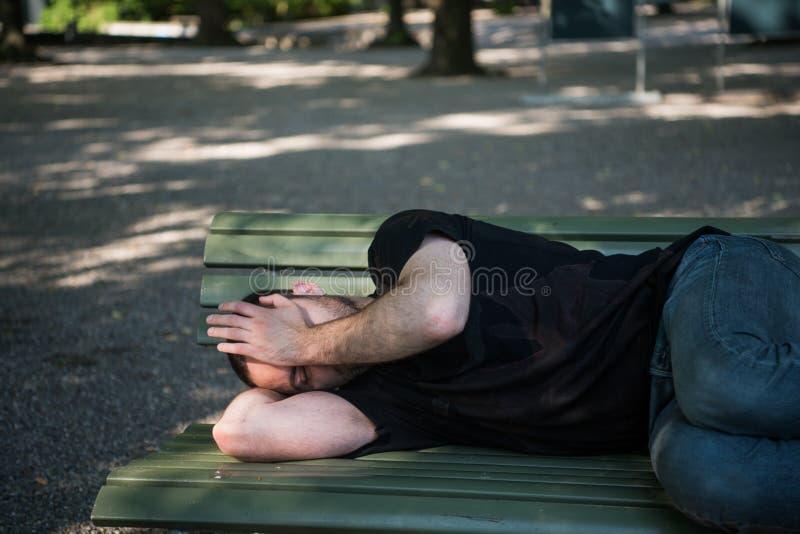 睡觉在长木凳的可怜的无家可归的人在公园 库存照片