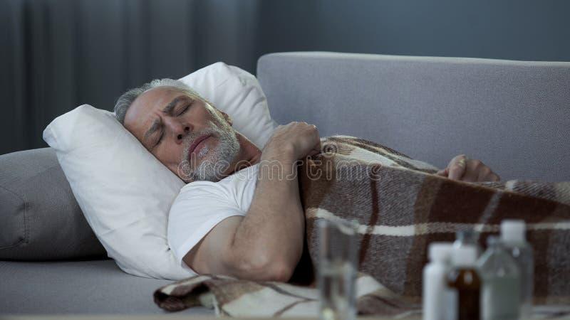 睡觉在长沙发的男性领抚恤金者,遭受高温,疾病 库存照片
