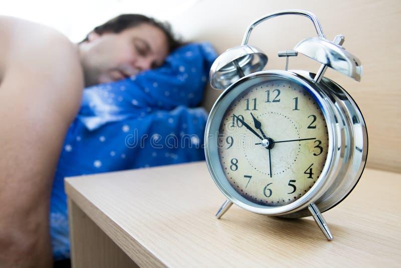 睡觉在闹钟旁边的床上的疲乏的人 免版税库存照片