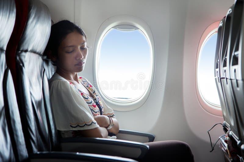 睡觉在飞机的妇女 库存照片
