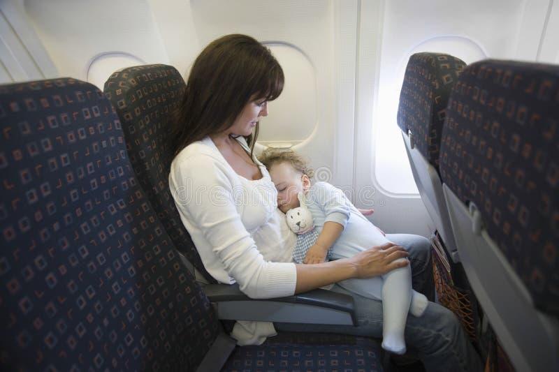 睡觉在飞机的母亲的膝部的婴孩 免版税库存图片