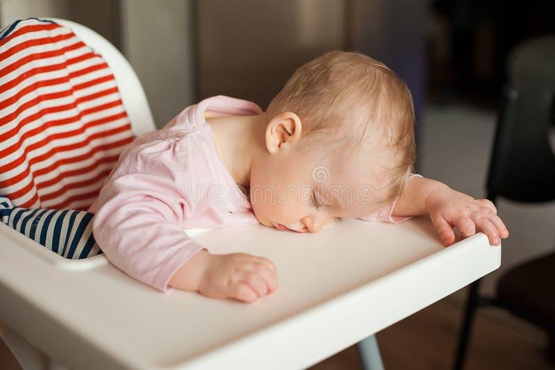 睡觉在高脚椅子的疲乏的孩子在午餐以后 girllying他的在桌盘子的逗人喜爱的婴孩面孔 免版税图库摄影