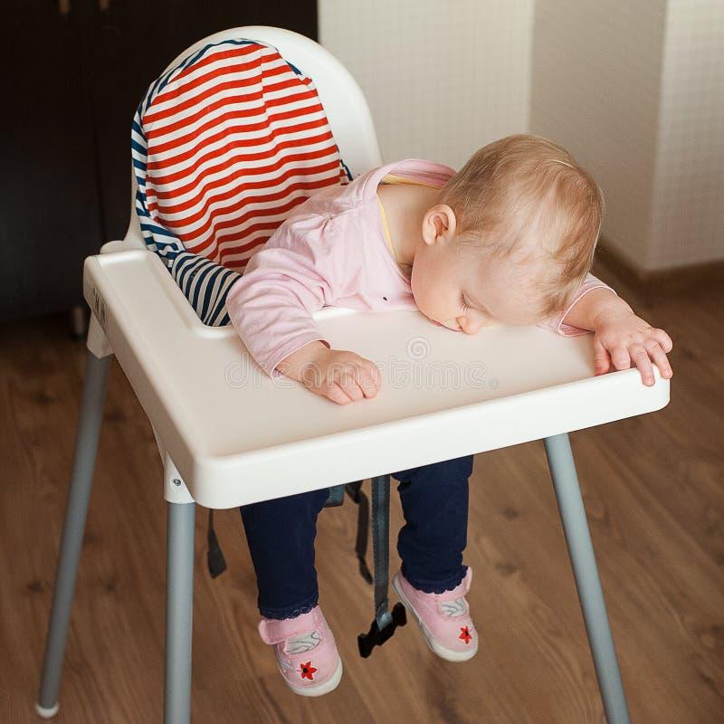 睡觉在高脚椅子的疲乏的孩子在午餐以后 girllying他的在桌盘子的逗人喜爱的婴孩面孔 图库摄影