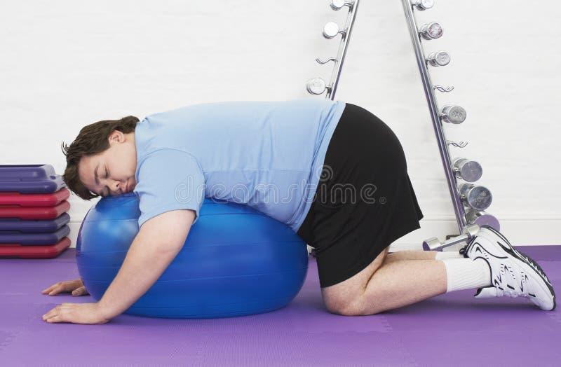 睡觉在锻炼球的超重人 库存图片
