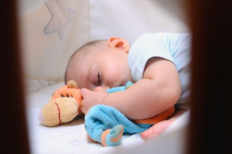睡觉在他的小儿床的婴孩 免版税库存图片