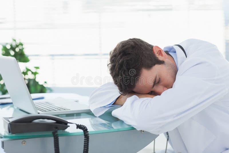 睡觉在他的甲板的疲乏的医生 免版税库存照片
