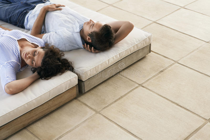 睡觉在Sunbeds的夫妇在手段 免版税库存图片