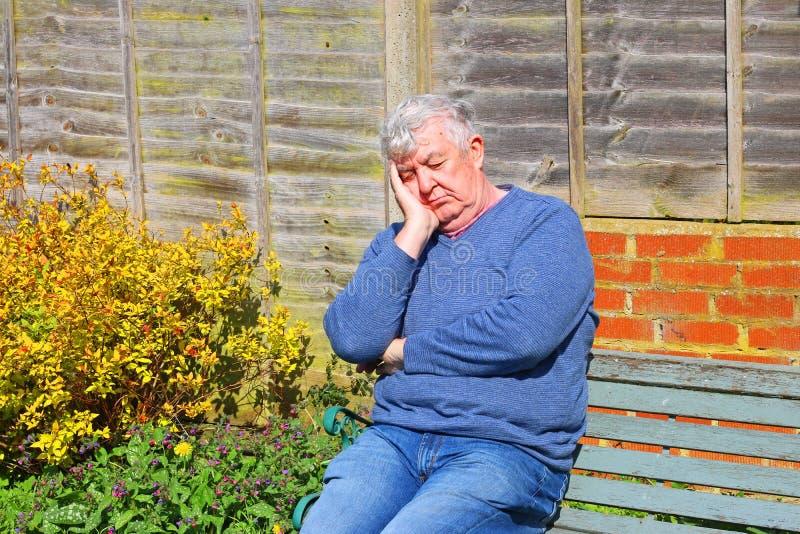 睡觉外面在长凳的老人 库存照片